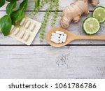 herbal pills in wooden spoon... | Shutterstock . vector #1061786786