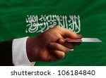 man stretching out credit card to buy goods in front of complete wavy national flag of saudi arabia - stock photo