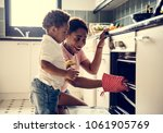 black kid helping mom baking... | Shutterstock . vector #1061905769