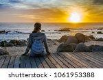 girl sits on a wooden bridge... | Shutterstock . vector #1061953388