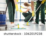 coworkers moping the floor and... | Shutterstock . vector #1062019238