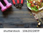 Fresh healthy salad with dumbbells and excercise equipment on wood background top viwe with copy space. For dieting, fitness and active healthy lifestyles Concept.