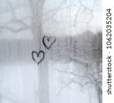 two hearts painted on a misted... | Shutterstock . vector #1062035204
