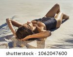 beautiful girl sunbathing on a... | Shutterstock . vector #1062047600