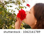 Young Woman Smells A Red Rose...