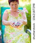 Small photo of Elderly woman holding daily antidiabetic pills dosage and vitamin.