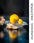 Small photo of Raw fresh ripe lemons or Citrus × limon in a glass squeezer on black wooden surface in dark Gothic colors with ayurvedic herb dried ginger it helps in digestion,relief of cough, it is antifungal herb.