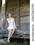 Small photo of A short-haired girl in a linen white dress is sitting barefoot, on the wooden threshold of an old farmhouse, against the backdrop of a door with bolts
