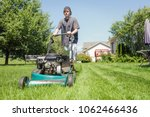 teenage boy mowing lawn | Shutterstock . vector #1062466436