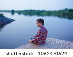child sitting on a wooden pier... | Shutterstock . vector #1062470624