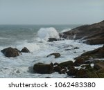 Small photo of a wave-ridden area, with rocks covered with white foam and in the background the gray ocean wind-churned, Santa Marta lighthouse, SC, Brazil