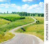winding asphalt road among... | Shutterstock . vector #1062632000
