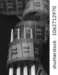 Small photo of fork and centimeter on a dark background. black and white photo