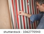 the process of gluing wallpaper ... | Shutterstock . vector #1062770543