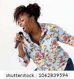 a woman vocalist singing karaoke | Shutterstock . vector #1062839594