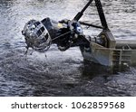 Small photo of Turning head of a small floating suction cutter dredger, lifted above water for inspection.