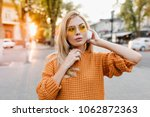 Tired adorable lady in orange sweater standing in city square and listening favorite song in headphones. Outdoor portrait of dreamy european girl wears sunglasses holding white earphones.