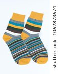 Small photo of A pair of striped socks. Stripes color: mostard, turquoise, white and gray. April of 2018.