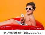 Small photo of Summer's lease hath all too short a date! Smiling good-looking little boy swimming with the rubber ring and eating ice-cream.
