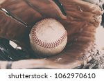 Small photo of Baseball in glove on ground, dirty game equipment