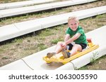 cute smiling young boy riding... | Shutterstock . vector #1063005590