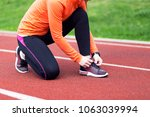 woman runner tying shoelace on... | Shutterstock . vector #1063039994
