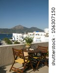 Small photo of patio table chairs view of harbor and town Adamas Milos Cyclades Greek Island Greece