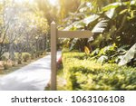 Small photo of True tilt-shift shot of a wooden blank waypoint marker located next to the footpath of a tropical resort and surrounded by palms, bushes and other plants; warm bright summer day, selective focus