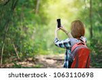 Small photo of tourism carry back pack and using cell phone in the forest