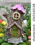 Small photo of Magical cute fairy house with flower roof and rock staircase in enchanted summer garden