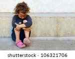 Stock photo poor sad little child girl sitting against the concrete wall 106321706