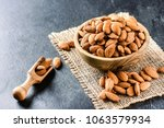 almonds on dark stone table.... | Shutterstock . vector #1063579934