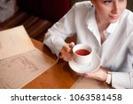 the girl sits at a table in a... | Shutterstock . vector #1063581458