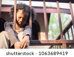 Stock photo little boy sitting behind the fence homeless orphan stressful kids education sickness human right 1063689419