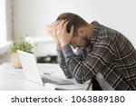 Small photo of Frustrated depressed man holding head in hands shocked by bankruptcy stock downfall sitting at work desk with laptop, stressed tired businessman feels despair lost money online or got problem debt