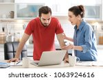 Small photo of Young couple having argument about family budget in kitchen