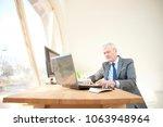 shot of a senior investment... | Shutterstock . vector #1063948964
