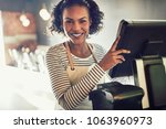 smiling young african waitress... | Shutterstock . vector #1063960973