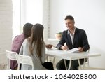 Small photo of Smiling financial advisor consulting interracial couple about new house at meeting, friendly architect real estate agent discussing building plan with family clients, mortgage loan investment concept