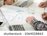 Small photo of Businessman signing two-sided indenture business contract concept, entrepreneur puts written signature on legal document making partnership deal, man fills document form at meeting, close up view