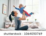 mother and her child playing... | Shutterstock . vector #1064050769