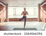 young woman practicing yoga in... | Shutterstock . vector #1064066396