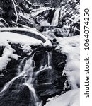 Small photo of Winter time hiking to the Sanderson Brook Falls in Chester MA. Snow and Ice cover the landscape in this large cascade.