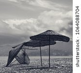 Small photo of Black and white old sunshade on deserted beach out of season and gray sky with clouds
