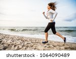 young woman running  jumping on ... | Shutterstock . vector #1064090489