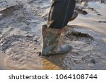 a man in large dirty rubber... | Shutterstock . vector #1064108744