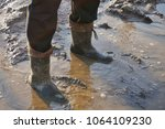 a man in large dirty rubber... | Shutterstock . vector #1064109230