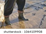 a man in large dirty rubber... | Shutterstock . vector #1064109908