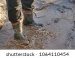 a man in large dirty rubber... | Shutterstock . vector #1064110454