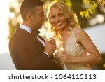 newlyweds drinking champagne on ... | Shutterstock . vector #1064115113